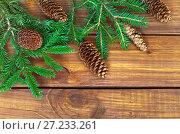 Купить «Еловые ветки и шишки на деревянном фоне. Новогодний фон», фото № 27233261, снято 22 ноября 2017 г. (c) Виктория Катьянова / Фотобанк Лори