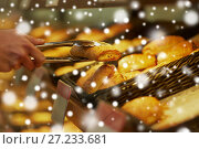 Купить «hand with tongs taking bun at bakery or grocery», фото № 27233681, снято 2 ноября 2016 г. (c) Syda Productions / Фотобанк Лори