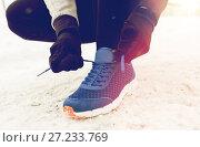 Купить «close up of man tying shoe lace in winter outdoors», фото № 27233769, снято 10 ноября 2016 г. (c) Syda Productions / Фотобанк Лори