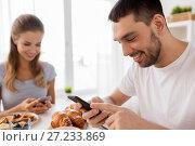 Купить «couple with smartphones having breakfast at home», фото № 27233869, снято 19 октября 2017 г. (c) Syda Productions / Фотобанк Лори