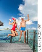 Купить «The man and the woman in New Year's Santa-Klaus cap jumps on background of sea», фото № 27234061, снято 15 июня 2011 г. (c) Куликов Константин / Фотобанк Лори