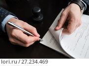 Купить «Мужчина ставит подпись под документами», эксклюзивное фото № 27234469, снято 6 ноября 2017 г. (c) Игорь Низов / Фотобанк Лори