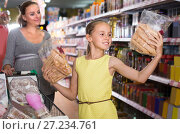 Купить «Girl 10-12 years old is showing purchases which they chosen with mother», фото № 27234761, снято 5 июня 2017 г. (c) Яков Филимонов / Фотобанк Лори
