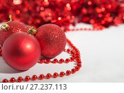 Купить «Christmas decorations of red color on a white background - balls, beads, tinsel», фото № 27237113, снято 23 ноября 2017 г. (c) Юлия Бабкина / Фотобанк Лори