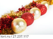 Купить «Christmas decorations of red and golden color on a white background - balls and tinsel», фото № 27237117, снято 24 ноября 2017 г. (c) Юлия Бабкина / Фотобанк Лори