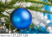 Купить «Christmas decorations, one blue ball hanging on the Christmas tree», фото № 27237129, снято 25 ноября 2017 г. (c) Юлия Бабкина / Фотобанк Лори