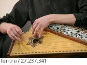 Купить «Музыкант играет на народном струнном инструменте гусли во время концерта», фото № 27237341, снято 17 ноября 2017 г. (c) Николай Винокуров / Фотобанк Лори