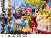 Купить «Family of three at Christmas market. Selective focus», фото № 27238037, снято 15 декабря 2016 г. (c) Яков Филимонов / Фотобанк Лори