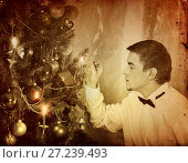 Купить «Man alone put up Christmas tree. Xmas party at home .», фото № 27239493, снято 10 ноября 2012 г. (c) Gennadiy Poznyakov / Фотобанк Лори