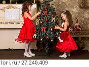 Купить «Две девочки в красных платьях наряжают елку», фото № 27240409, снято 17 декабря 2015 г. (c) Марина Володько / Фотобанк Лори