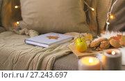 Купить «book, autumn leaves, nuts and cookies on sofa», видеоролик № 27243697, снято 23 ноября 2017 г. (c) Syda Productions / Фотобанк Лори