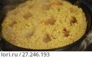 Купить «Cooking pilaf, pilaf is boiling in cast-iron kettle», видеоролик № 27246193, снято 2 октября 2017 г. (c) Ирина Мойсеева / Фотобанк Лори