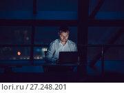 Купить «Businessman working on laptop in night office.», фото № 27248201, снято 8 ноября 2017 г. (c) Женя Канашкин / Фотобанк Лори