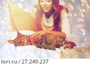 Купить «happy young woman with cat lying in bed at home», фото № 27249237, снято 15 октября 2016 г. (c) Syda Productions / Фотобанк Лори