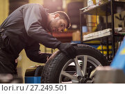 Купить «auto mechanic balancing car wheel at workshop», фото № 27249501, снято 21 сентября 2017 г. (c) Syda Productions / Фотобанк Лори