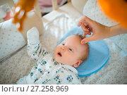 Купить «The baby is in the crib and looks at toys», фото № 27258969, снято 27 августа 2017 г. (c) Dmitry Chapurin / Фотобанк Лори