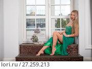 Купить «Девушка в зелёном платье сидит на подоконнике», фото № 27259213, снято 28 октября 2017 г. (c) Литвяк Игорь / Фотобанк Лори