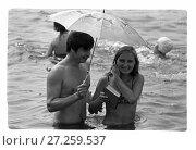 Купить «Мужчина и девушка с книгой под зонтом стоят по пояс в реке», фото № 27259537, снято 23 февраля 2019 г. (c) Борис Кавашкин / Фотобанк Лори