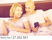 Купить «mature couple reading with smartphones in bedroom interior», фото № 27262561, снято 31 мая 2020 г. (c) Яков Филимонов / Фотобанк Лори