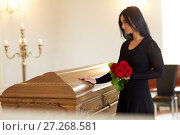 Купить «sad woman with red rose and coffin at funeral», фото № 27268581, снято 20 марта 2017 г. (c) Syda Productions / Фотобанк Лори