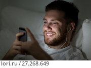 Купить «man with smartphone and earphones in bed at night», фото № 27268649, снято 26 ноября 2016 г. (c) Syda Productions / Фотобанк Лори
