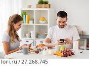 Купить «couple with smartphones having breakfast at home», фото № 27268745, снято 19 октября 2017 г. (c) Syda Productions / Фотобанк Лори