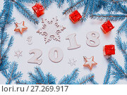 Купить «New Year 2018 background with figures, Christmas toys, with frame of green fir branches. New Year 2018 composition. Flat lay, top view of New Year 2018 festive still life», фото № 27269917, снято 30 ноября 2016 г. (c) Зезелина Марина / Фотобанк Лори