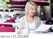 Купить «Portrait of elegant mature female who is reading documents in time lunch with coffee», фото № 27270869, снято 3 сентября 2017 г. (c) Яков Филимонов / Фотобанк Лори