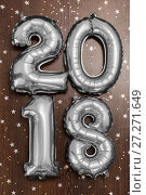 Купить «Bright metallic silver balloons figures 2018, Christmas, New Year Balloon with glitter stars on dark wood table background», фото № 27271649, снято 19 ноября 2017 г. (c) Сергей Тимофеев / Фотобанк Лори