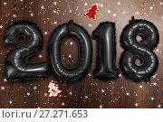 Купить «Bright metallic black balloons figures 2018, Christmas, New Year Balloon with glitter stars on dark wood table background», фото № 27271653, снято 19 ноября 2017 г. (c) Сергей Тимофеев / Фотобанк Лори