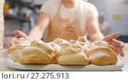 Купить «Cook carrying the fresh hot pastries in the bakery», видеоролик № 27275913, снято 27 июня 2019 г. (c) Константин Шишкин / Фотобанк Лори