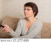 Купить «Женщина пенсионного возраста перед телевизором с пультом в руке», фото № 27277689, снято 10 декабря 2017 г. (c) Юлия Бабкина / Фотобанк Лори