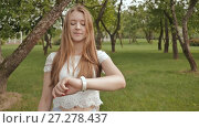 Купить «A young girl is engaged in a walk in the park, looking at a smart clock on her arm and receiving a pulse measurement. Health. Sport. Recreation. Summer.», видеоролик № 27278437, снято 21 октября 2017 г. (c) Mikhail Davidovich / Фотобанк Лори
