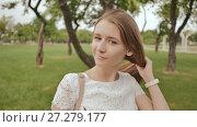 Купить «Beautiful student girl, smiling, combs her long hair in the park. Rest during study.», видеоролик № 27279177, снято 21 октября 2017 г. (c) Mikhail Davidovich / Фотобанк Лори