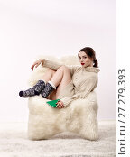 Купить «Brunette woman on furry arm-chair with book in hands», фото № 27279393, снято 8 октября 2017 г. (c) Serg Zastavkin / Фотобанк Лори