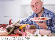 Купить «man posing with a plate of cold cuts», фото № 27283749, снято 17 ноября 2016 г. (c) Татьяна Яцевич / Фотобанк Лори