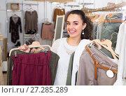 Купить «Girl selecting new garments at the store», фото № 27285289, снято 15 сентября 2019 г. (c) Яков Филимонов / Фотобанк Лори