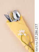 Купить «Cutlery wrapped in a yellow napkin on a light peach background.», фото № 27286217, снято 22 мая 2019 г. (c) Olesya Tseytlin / Фотобанк Лори