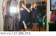 Stylish curly haired woman in evening dress posing for photographer in clothing store boutique. Стоковое видео, видеограф Константин Шишкин / Фотобанк Лори