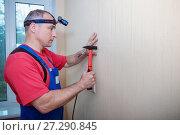 Купить «Hammer a nail in wall. Worker with hammer.», фото № 27290845, снято 21 мая 2017 г. (c) Наталья Давыдова / Фотобанк Лори