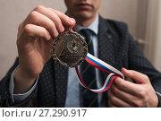 Купить «Бизнесмен держит в руках медаль за 2 место», эксклюзивное фото № 27290917, снято 6 ноября 2017 г. (c) Игорь Низов / Фотобанк Лори