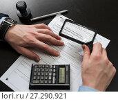 Купить «Бизнесмен рассматривает налоговую декларацию на вменённый доход через лупу», эксклюзивное фото № 27290921, снято 6 ноября 2017 г. (c) Игорь Низов / Фотобанк Лори
