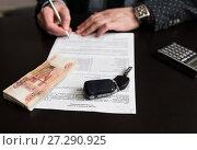 Купить «Покупка автомобиля. Российские деньги и автомобильный ключ от зажигания  на фоне мужчины подписывающего  договор купли продажи», эксклюзивное фото № 27290925, снято 6 ноября 2017 г. (c) Игорь Низов / Фотобанк Лори