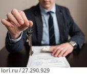 Купить «Бизнесмен протягивает ключи от квартиры на фоне документов и денег», эксклюзивное фото № 27290929, снято 6 ноября 2017 г. (c) Игорь Низов / Фотобанк Лори