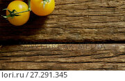 Купить «Yellow cherry tomatoes with stem on wooden floor 4K 4k», видеоролик № 27291345, снято 21 апреля 2018 г. (c) Wavebreak Media / Фотобанк Лори