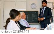 Купить «Employees are demonstrating reports on laptop to mature boss in the office.», видеоролик № 27294141, снято 5 июля 2017 г. (c) Яков Филимонов / Фотобанк Лори