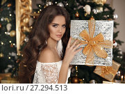Купить «Christmas. Beautiful smiling woman with gift box. fashion interior photo of gorgeous brunette. Makeup. Healthy long hair style. Elegant lady in white dress over golden xmas tree lights background.», фото № 27294513, снято 29 ноября 2017 г. (c) Photobeauty / Фотобанк Лори
