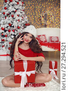 Купить «Christmas girl portrait in winter hat. Beautiful santa woman present gift box. Smiling brunette in red with long hair sitting on chunky yarn blanket in home over xmas tree bokeh lights background.», фото № 27294521, снято 29 ноября 2017 г. (c) Photobeauty / Фотобанк Лори