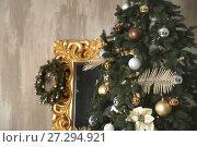 Купить «Closeup of Christmas tree decoration with wreath on golden frame mirror leaning on wall», фото № 27294921, снято 29 ноября 2017 г. (c) Photobeauty / Фотобанк Лори