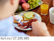Купить «man eating toast with mozzarella, egg and bacon», фото № 27295985, снято 5 октября 2017 г. (c) Syda Productions / Фотобанк Лори
